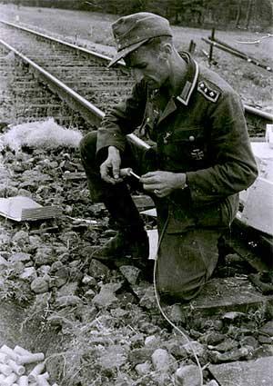 Немецкий сапер готовится к подрыву железной дороги перед отступлением