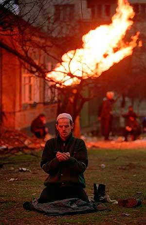 Чеченец молится в Грозном, январь 1995 г. На заднем фоне горит перебитая осколками газовая труба
